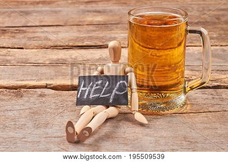 Help to get rid of alcohol. Human wooden figurine with message help, glass of beer, old wooden background.