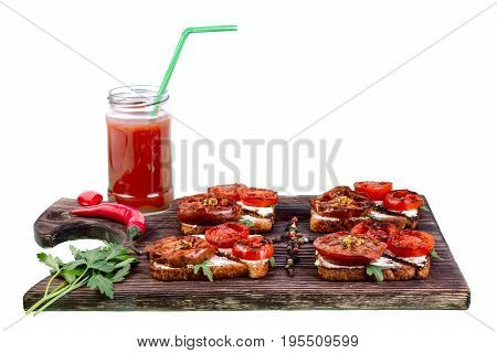 Sandwiches with grilled tomatoes lie on the cutting board. Tomato juice in a glass with a straw. Isolated on white background.