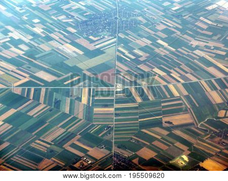 View from airplane window to farmland and road. Colors toned.