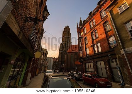 Church and vintage houses on the street in old town of Gliwice Poland Europe.
