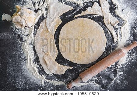 Baking pizza concept. Rolled out thin dough and rolling pin on black background. Cooking pastry