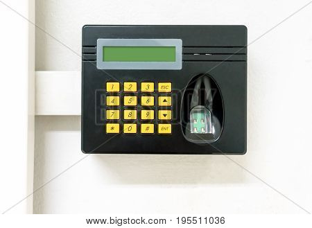 Black biometric scan with laser fingerprint sensor and digital screen for staff check-in on white wall