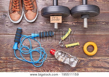 Sportsman equipment for physical training. Shoes, dumbbells, jumping rope, expander, bottle, wooden floor.