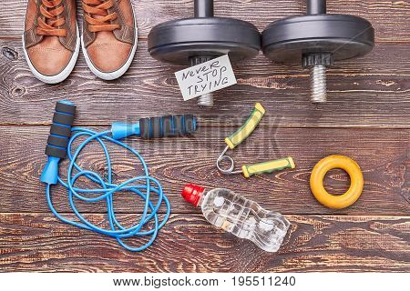 Sport equipment background. Sport shoes, jumping rope, dumbbells, expanders, bottle, message, wooden background.