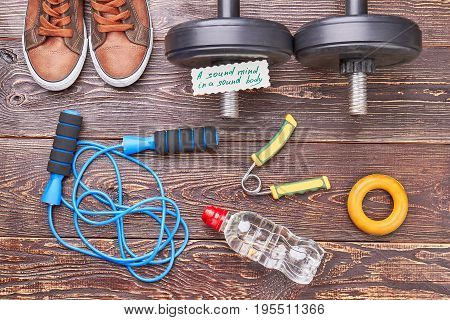 Gym equipment background. Expanders, jumping rope, dumbbells, shoes, water, message on rustic wooden background.