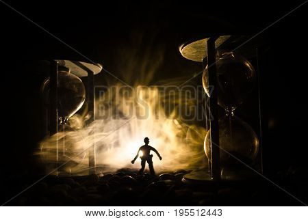 Time Concept. Silhouette Of A Man Standing Between Hourglasses With Smoke And Lights On A Dark Backg