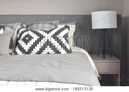 Graphic Pattern And Grey Shade Pillows On The Bed With Modern Style Reading Lamp