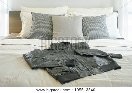 Gray Pillows And Black Leather Jacket On Bed
