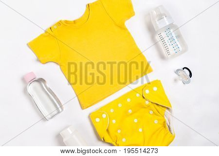 Yellow children's costume, bottle and orthodontic pacifier on a white background. Top view. Copy space. Flat lay. Still life