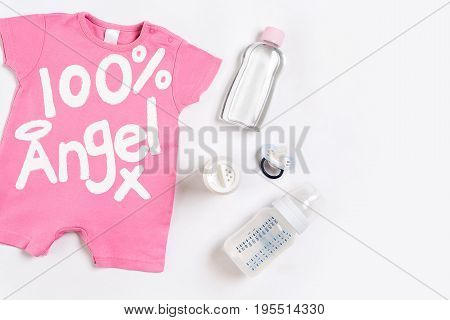 Pink children's costume, bottle and orthodontic pacifier on a white background. Top view. Copy space. Flat lay. Still life