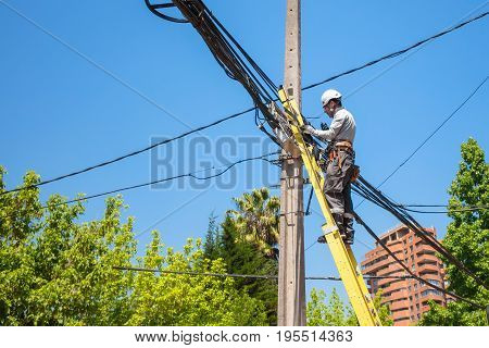 SANTIAGO CHILE - NOVEMBER 11 2016: Electrician fixing the cables on the pole of the city network. This work needs high safety requirements.