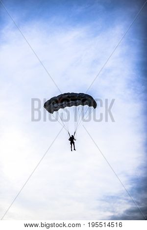 Silhouette of parachuter on a blue sky with clouds on it.