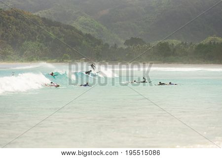 10/06/2017 Pantau Mawun Lombok Indonesia. Large group of tourists learn to surf on small beginner waves at a paradise tropical beach.