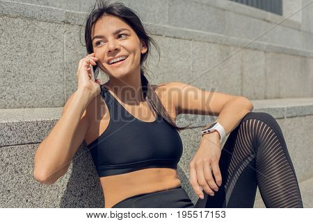 Young female active exercise workout on street outside phone call