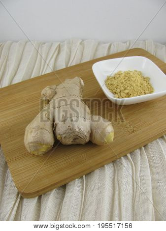 Fresh ground ginger and ginger root on a wooden board