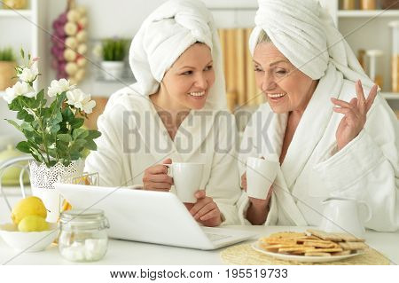 Mother and daughter in white bathrobes sitting at kitchen table with laptop