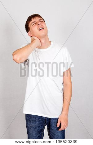 Young Man feels Pain in the Neck on the White Wall Background