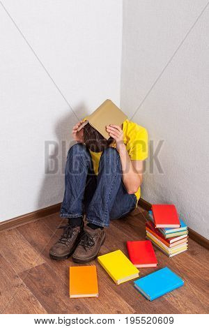 Sad Teenager with a Books on the Floor in the Corner