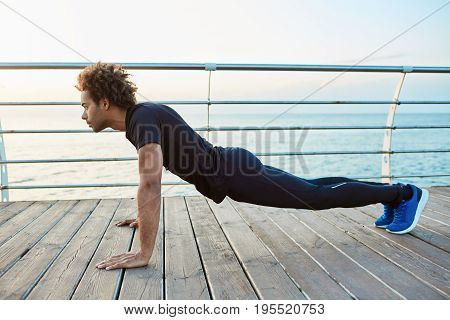 Confident dark-skinned muscled young sportsman wearing sport wear and doing plank position while exercising on the wooden floor of embankment. Enjoying sport early in the morning by the sea.