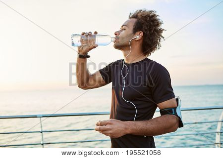 Slim and young sportsman refreshing himself, drinking water out of plastic bottle in the morning sunlight. Listening to his favourite songs while jogging. Young Afro-American practicing healthy lifestyle.