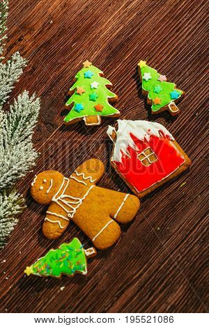 painted gingerbread house, Christmas tree and the man on a wooden background.