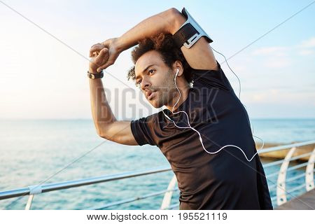 Dark-skinned male runner with beautiful athletic body and bushy hairstyle stretching muscles, raising his arms while warming up before morning workout session. Sportsman exercising by the sea wearing white earphones.
