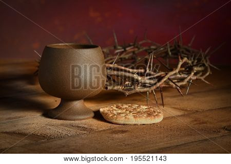 Communion table with bread and cup of wine and crown of thorns in background