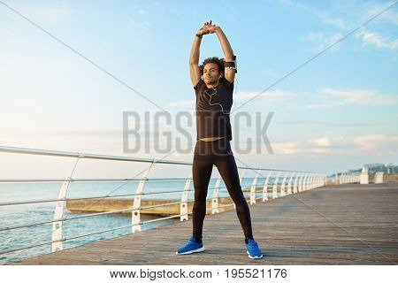 Healthy lifestyle concept. Sporty dark-skinned boy in black sportswear and headphones standing on wooden platform, using smart phone technology to listen to music during run and stretching his arms. Outdoors training.