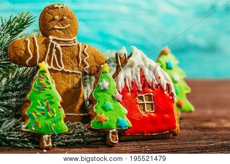 painted gingerbread house, Christmas tree and the man on a blue background.