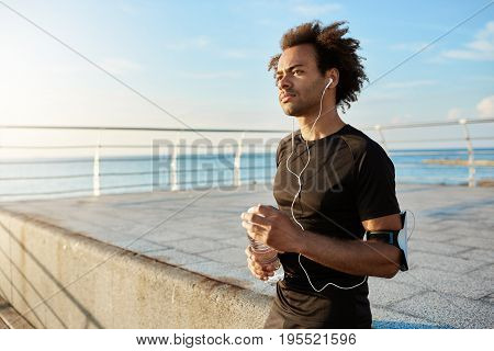Stylish male jogger with bushy hairstyle looking straightforward in the morning, enjoying sport activities. Fit man in earphones with bottle of water in hands taking break in the middle of training.