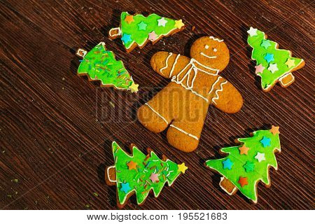 painted gingerbread Christmas tree and the man on a wooden background.
