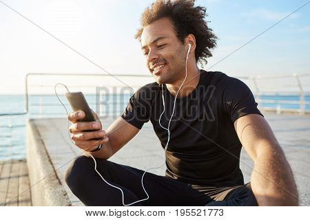 Stylish male dark-skinned athlete with Afro hairstyle using mobile phone, smiling, choosing best song for training. Smiling sportsman sitting on a wooden pier and messaging after jogging outdoors.