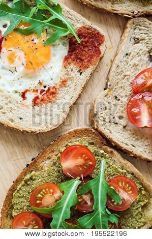Vertical photo of healthy toasts with multicereal bread cherry tomato egg arugula pesto sauce tomato sauce on wooden table
