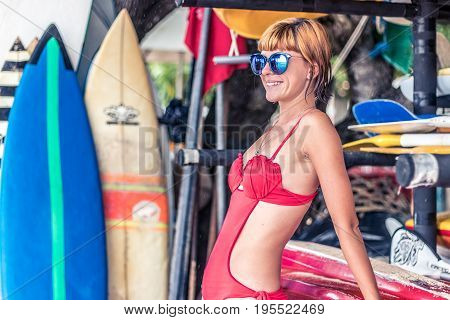 Young sexy girl in red swimsuit - surfer with surf board posing on the Nusa Dua beach, tropical Bali island. Family lifestyle, people water sport lessons and beach swimming activity on summer vacation.