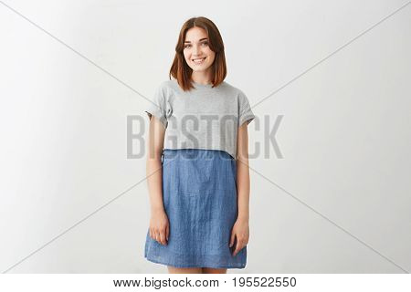 Portrait of young happy cheerful beautiful girl smiling looking at camera over white background. Copy space.