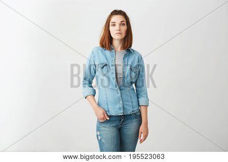 Portrait of young beautiful brunette girl looking at camera over white background. Copy space.