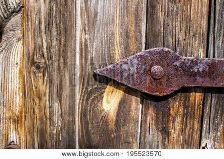 Old wooden door background and texture and rusty metal hinge