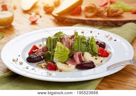 Spicy salad with beef and sun-dried tomatoes. Salad with pear, mushrooms, strawberries and greens. Tasty dish in white plate on wooden table. Close-up