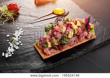 fresh tuna tartar with salt and herbs, studio shot. Fish tartar on black shale. Close-up