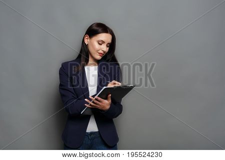 Busy elegant business woman in formal suit writing down notes to notepad, gray studio background.