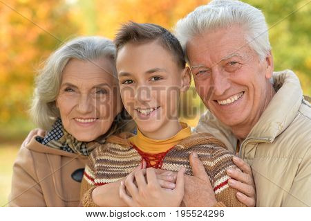 happy grandfather, grandmother  and grandson hugging  in park
