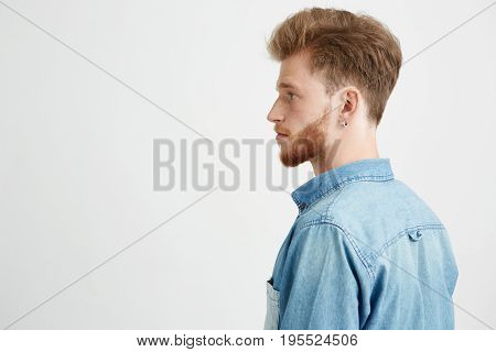 Portrait of young handsome man with beard wearing jean shirt standing in profile over white background. Copy space.