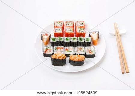 Traditional japanese food delivery. Sushi set served on white plate and chopsticks aside. Colorful rolls and gunkan assortment at white background, pov, copy space