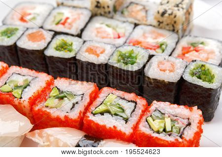 Japanese food restaurant delivery, closeup of colorful rolls and sushi platter at white background