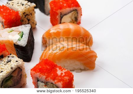 Traditional japanese restaurant food. Colorful rolls and sushi with salmon closeup at white with copy space. Big party sushi set, pov, sushi assortment background