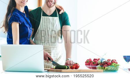 Young man cutting vegetables and woman standing with laptop in the kitchen.