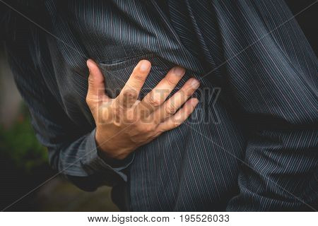 businessman having chest pain and heart attack hand holding the painful. businessman having heart attack.