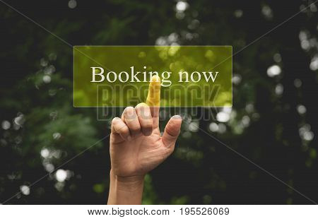Hand of person presses button booking now. Hand pressing on virtual screen and selecting booking now.