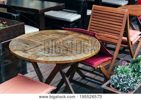 Round wooden table and chairs in a street cafe or restaurant