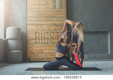 Yoga teacher and beginner in class, making asana exercises. Mermaid pose. Healthy lifestyle in fitness club. Stretching with coach